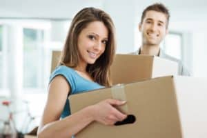 couple moving in a new house and carrying carton boxes